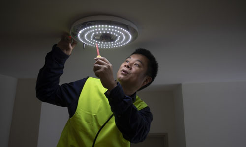 A man checking out the light meshed into the smart building network